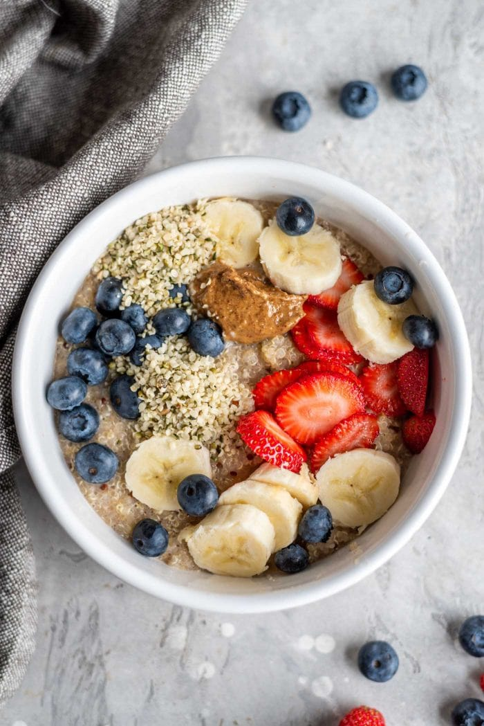 5-minute breakfast quinoa in a white bowl topped with berries, banana, hemp seeds and almond butter.