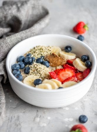 Hot breakfast quinoa in a white bowl with berries, almond butter and banana.