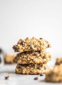 Stack of three gluten-free vegan chocolate chip quinoa cookies against a grey background.
