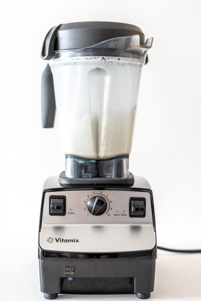 Vitamix blender with blended hemp milk in it.