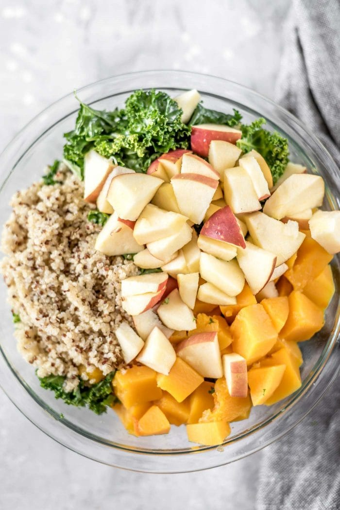 Chopped apple, cooked squash, quinoa and kale in a large glass mixing bowl.