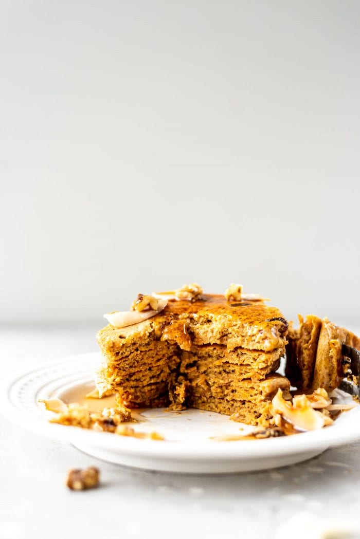 Stack of vegan gluten-free carrot cake pancakes on a small white plate.