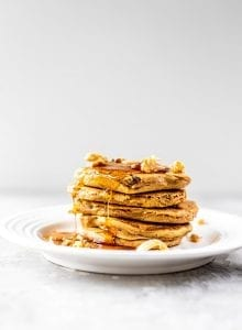 Stack of vegan gluten-free carrot cake pancakes with maple syrup, coconut and walnut topping.