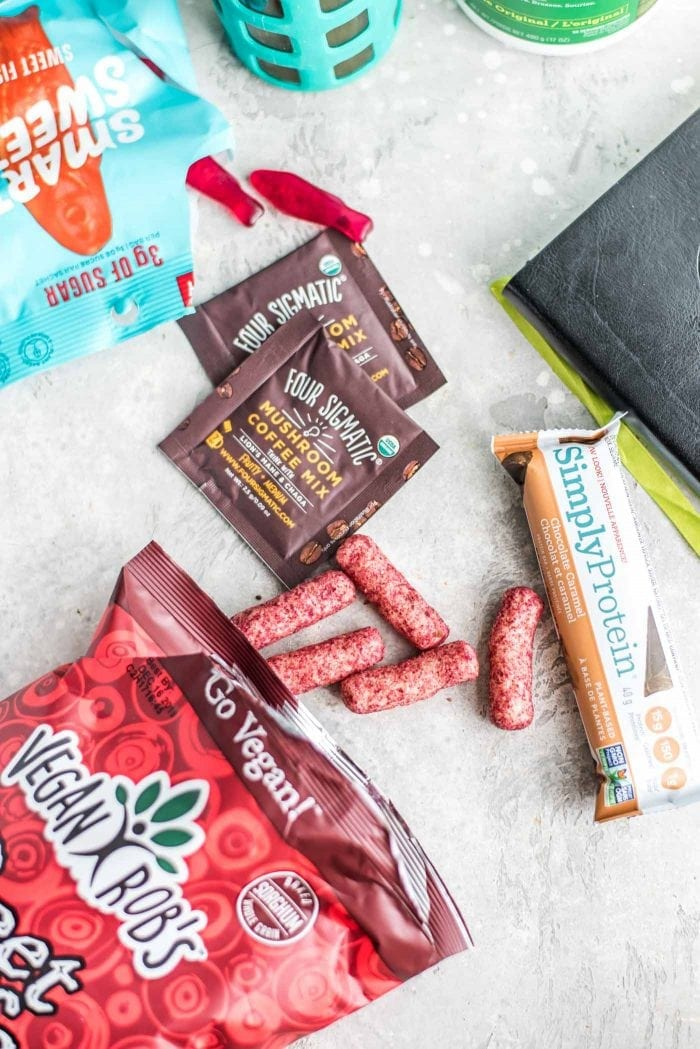 Vegan Robbs, Simply Protein Bars and other healthy snacks on a grey surface.