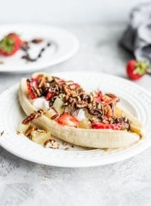 A vegan banana split with dairy-free yogurt, pecans and strawberries on a white plate.