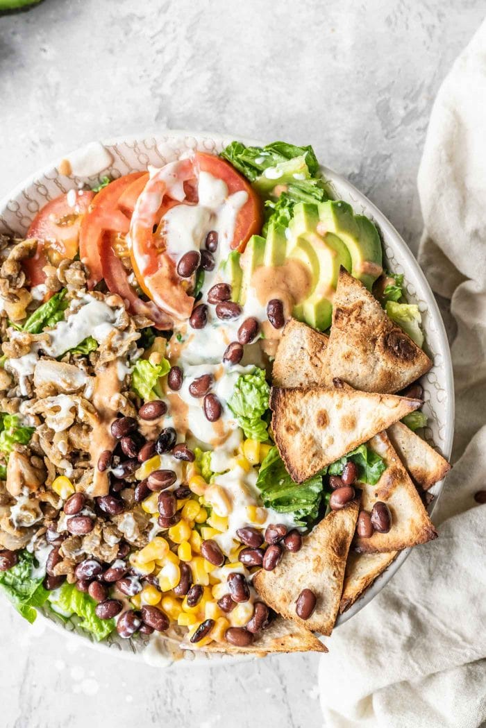 Taco salad with tortilla chips, corn, black beans, lentils and tomato.
