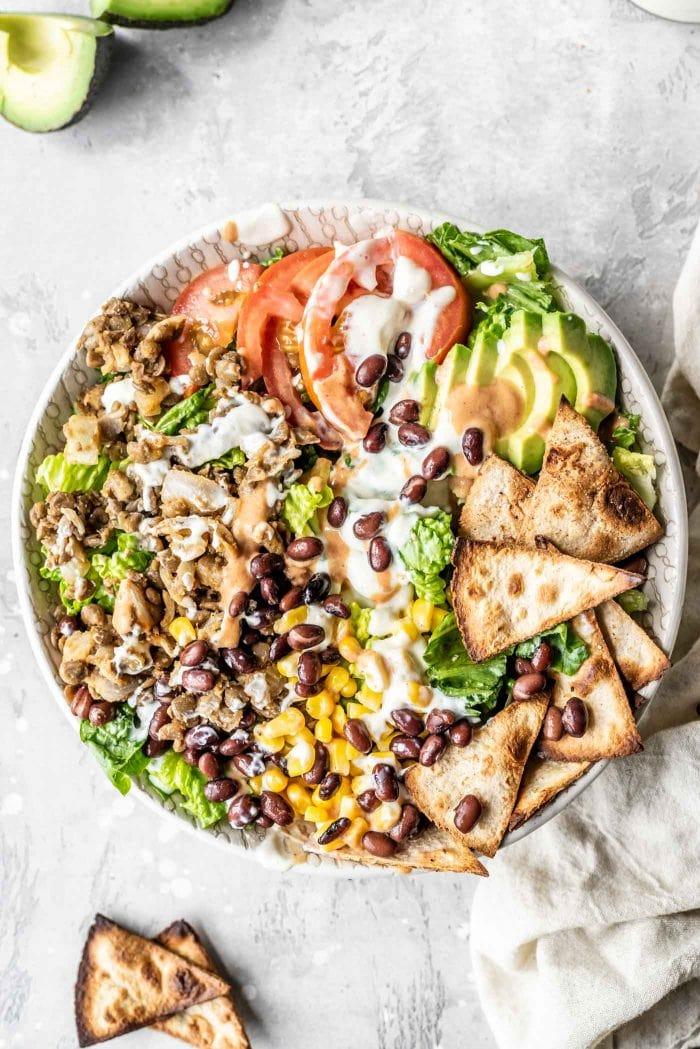 Vegan taco salad with lentils, tomato, corn, avocado and tofu sour cream in a bowl.