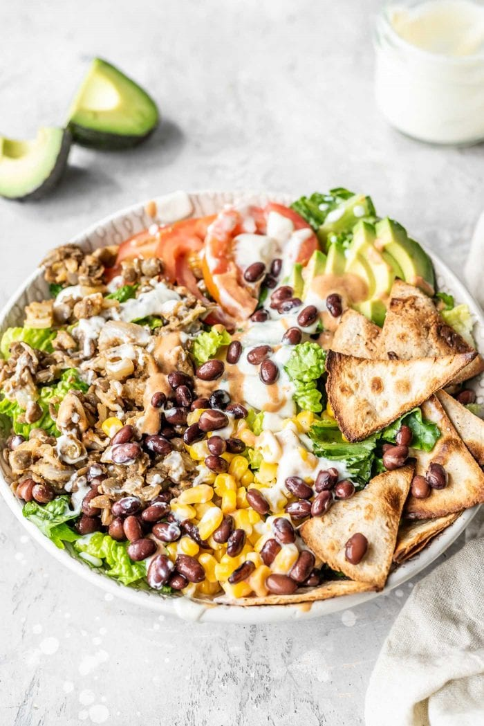 Healthy taco salad with avocado, corn, black beans and sour cream.