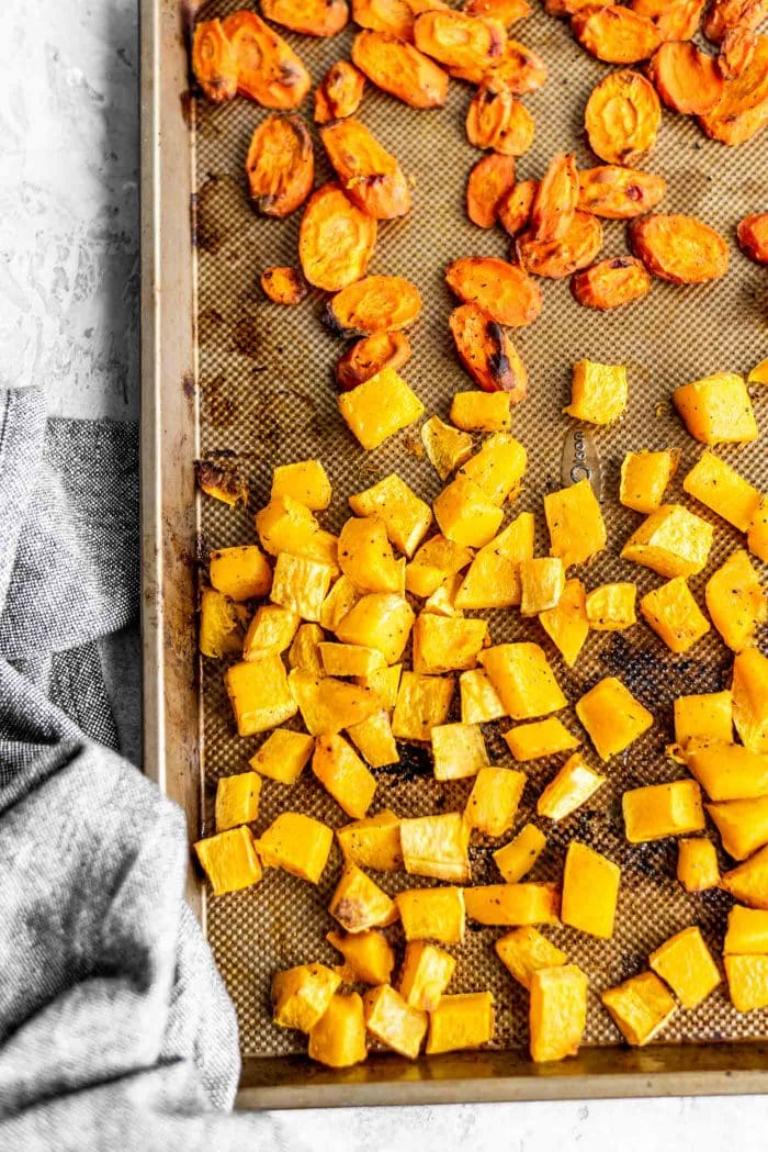 Roasted squash and carrot on a baking tray.