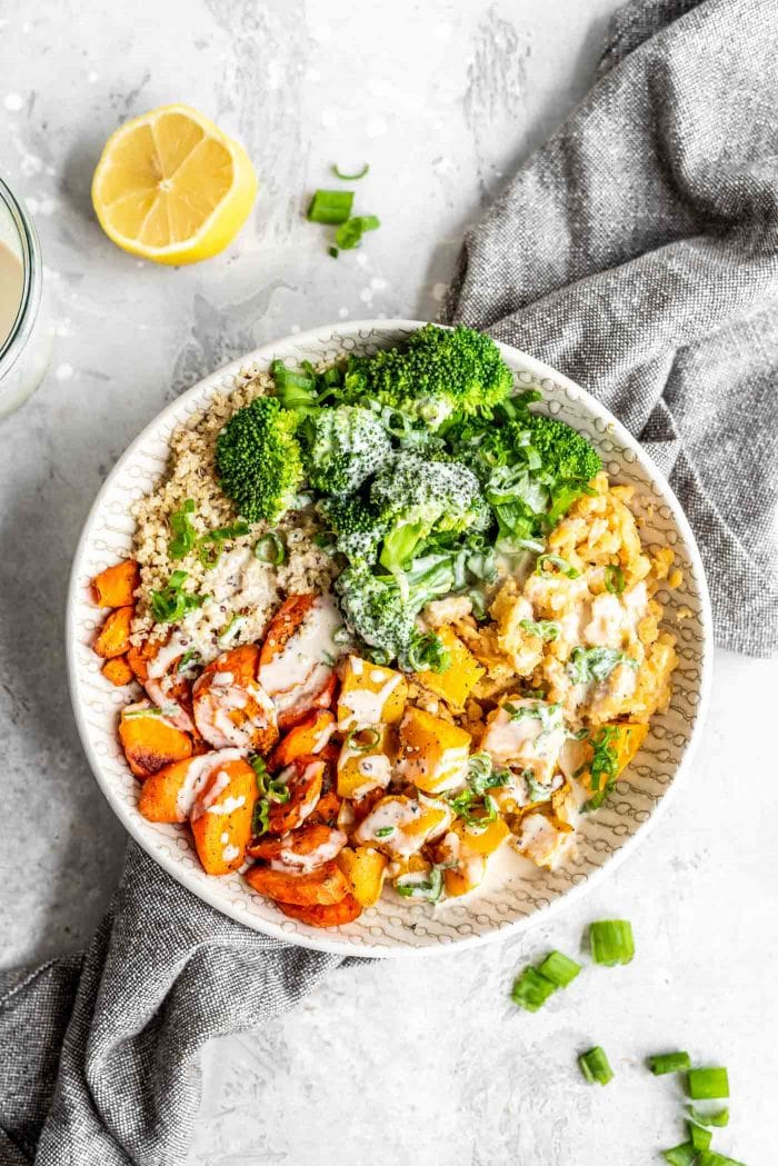 Roasted squash and carrots with red lentils, quinoa, broccoli and tahini sauce in a bowl.