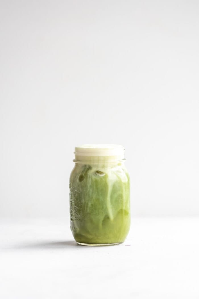 Dairy-free almond milk iced matcha latte in a glass jar against a white background.