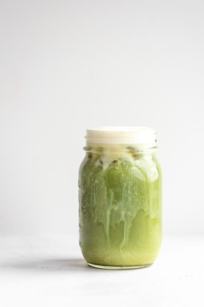 Jar of iced matcha on a grey background.