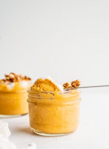 A spoon scooping pumpkin mousse out of a jar.