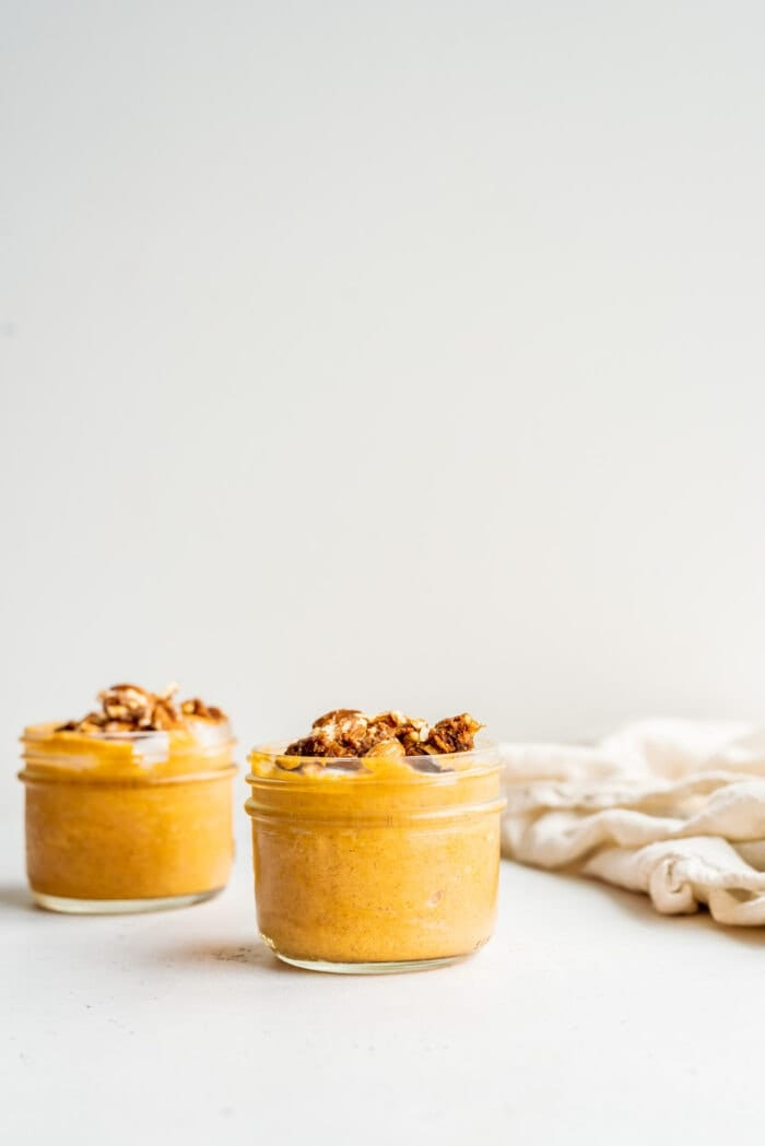 Two jars of pumpkin mousse topped with yogurt, nuts and dates.