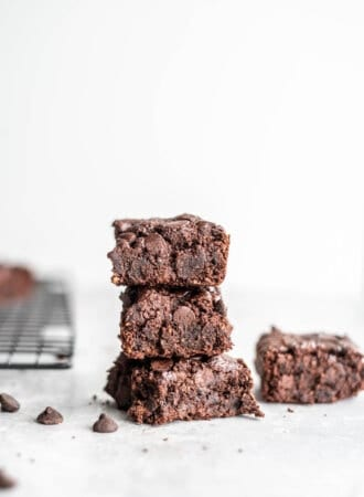 Stack of 3 vegan oat flour brownies on a grey surface with some chocolate chips scattered around.