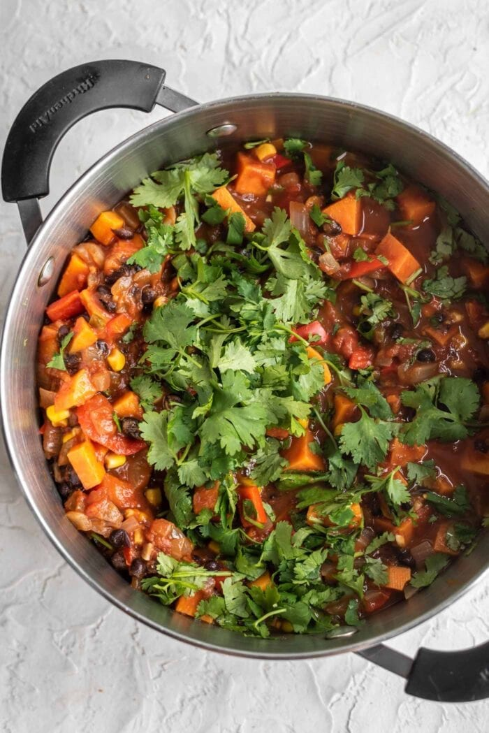 Sweet potato chili in a large soup pot topped with fresh, chopped cilantro.
