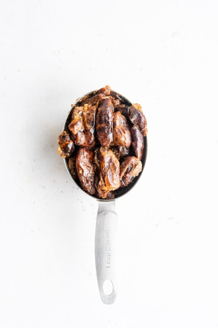 A 1 cup measuring cup packed with pitted dates.
