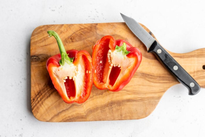 A red pepper cut in half on a cutting board with a knife.