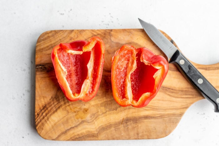 A red pepper cut in half with the seeds removed on a cutting board with a knife.