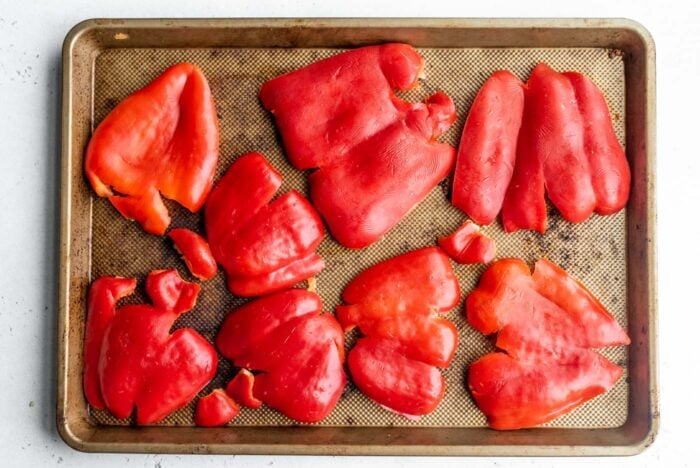 Smashed red bell peppers on a baking tray.