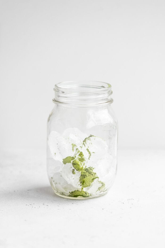 Ice and green tea matcha powder in a small glass mason jar.