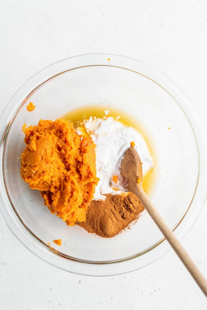 Pumpkin puree, pumpkin pie spice, coconut cream and maple syrup in a bowl.