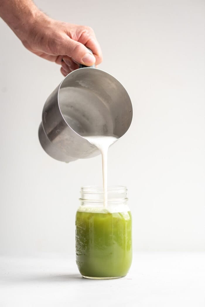 A hand pouring foamed almond milk into matcha in a jar using the Breville Milk Cafe.