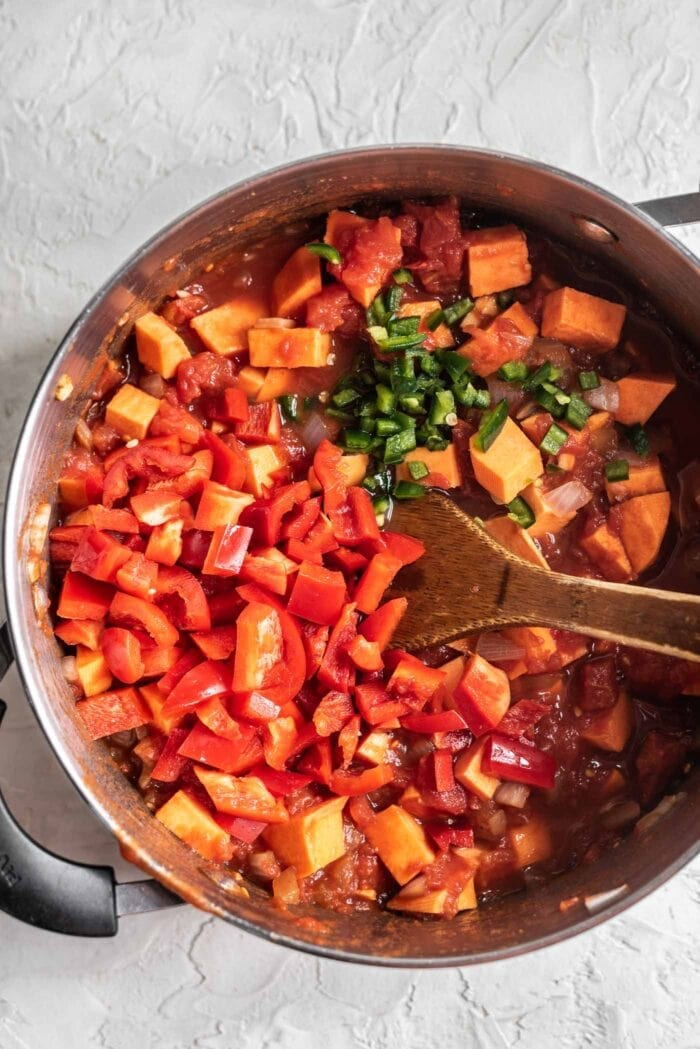 Red pepper and jalapeno being added to a large pot of chili.