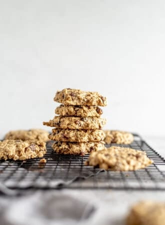 A stack of vegan and gluten-free, healthy oat cookies sitting on brown paper with some raisins scattered around.