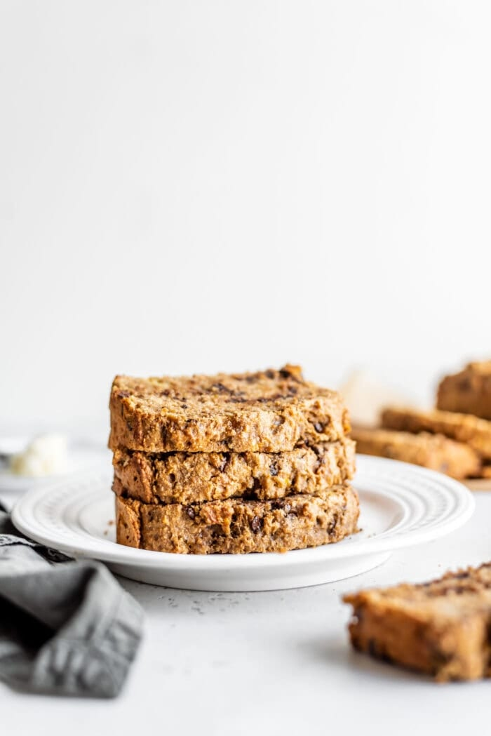 Stack of 3 slices of easy vegan banana bread on a white plate.