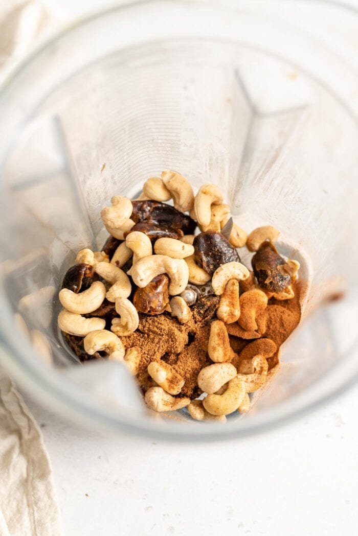 Cashews, dates, nutmeg and cinnamon in a blender container.