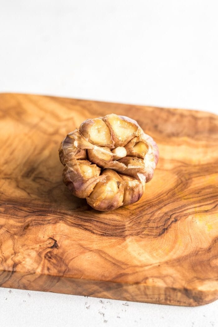 A whole bulb of roasted garlic on a cutting board.