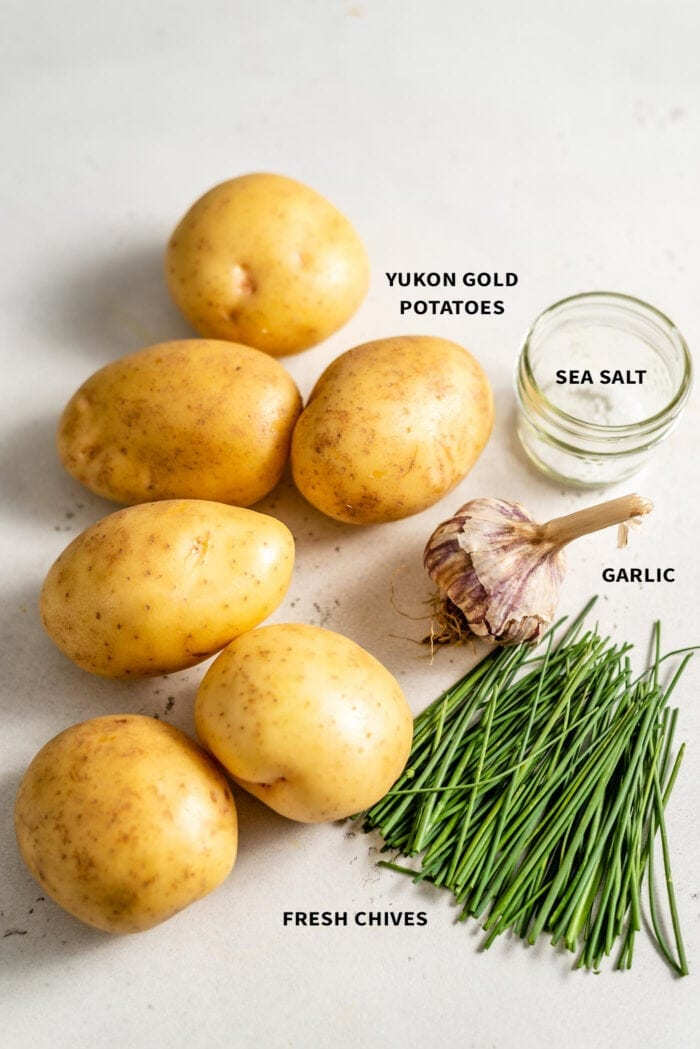6 Yukon Gold potatoes, sea salt, fresh chives and a bulb of garlic sitting on a white surface.