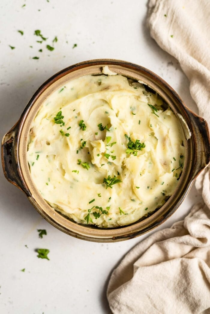 A serving dish full of vegan mashed potatoes topped with fresh chopped parsley and chives.