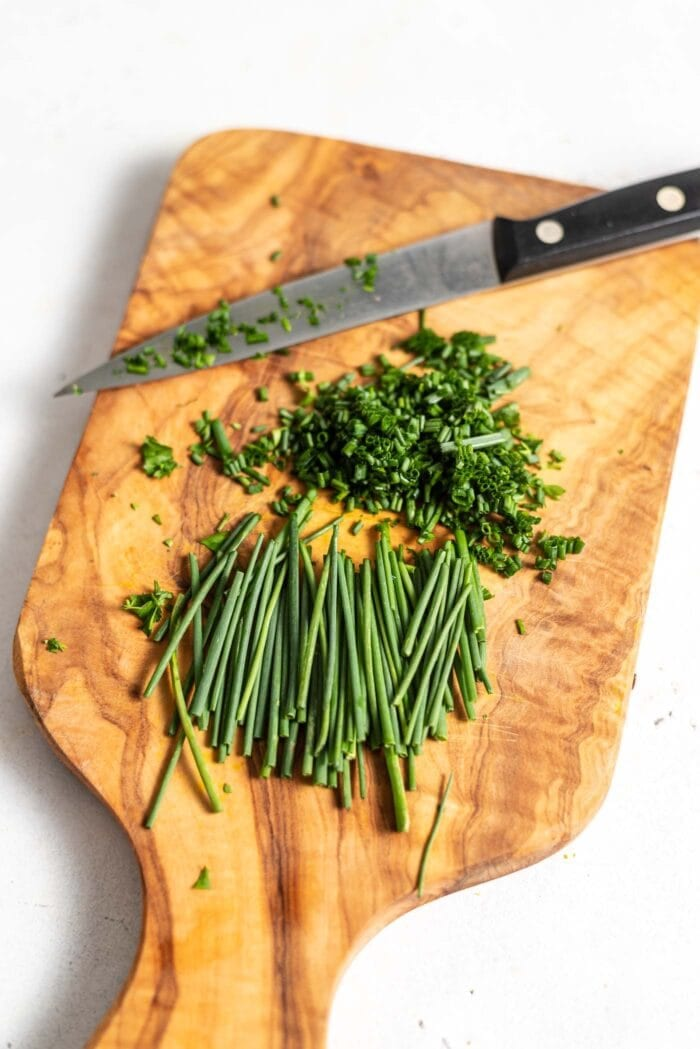 Chopped chives and a knife on a cutting board.
