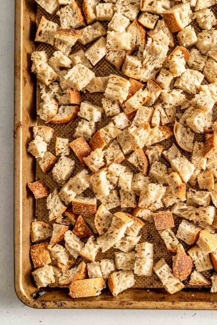 Cubed bread on a baking tray.