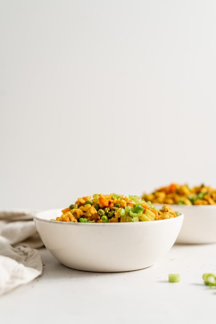 Two bowls of vegan fried brown rice with a few pieces of green onion scattered around.