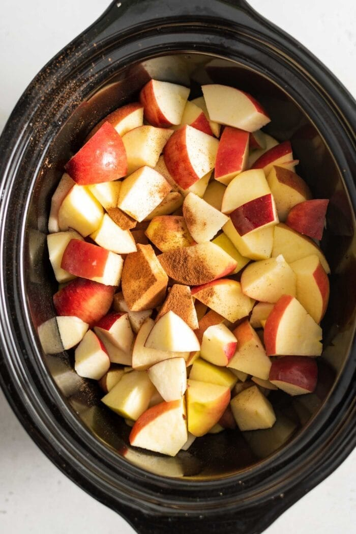 Chopped apples with cinnamon and nutmeg in a slow cooker.