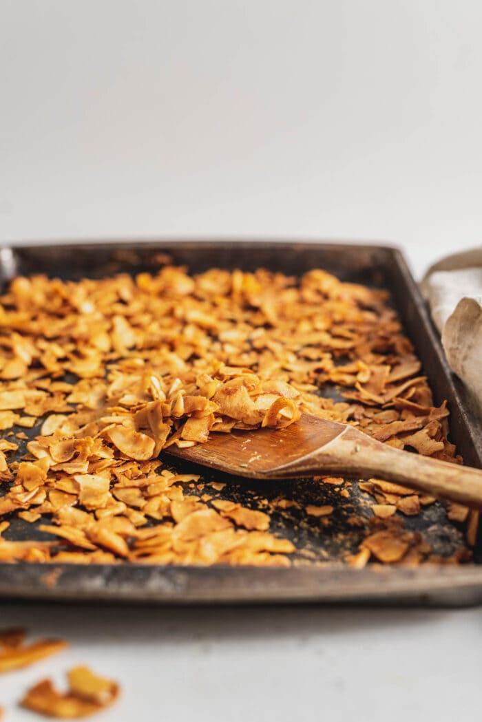 Coconut bacon on a baking try with a wooden spatula.