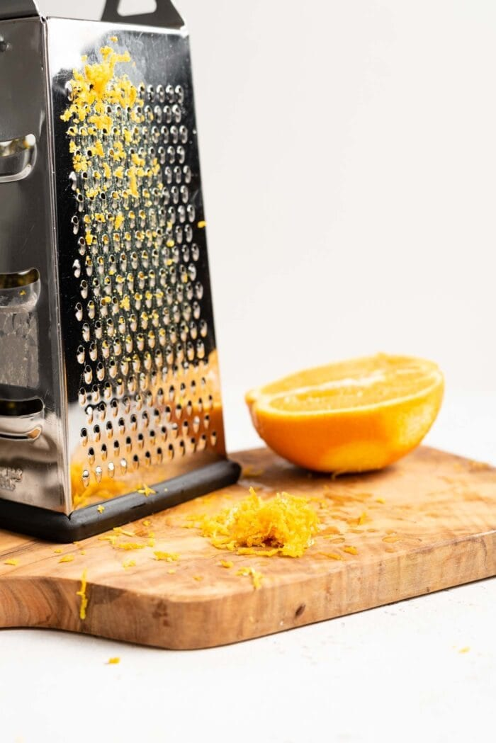 Orange zest, a box grater and a half a sliced navel orange sitting on a chopping board.