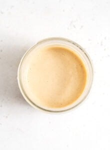 Creamy miso tahini dressing in a small glass jar.