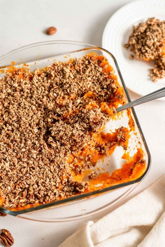 A serving spoon scooping out healthy vegan sweet potato casserole from a baking dish.