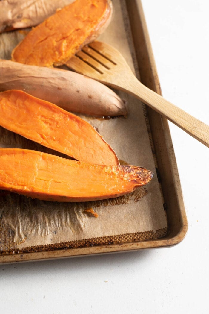 Roasted sweet potato on a baking tray lined with parchment paper.