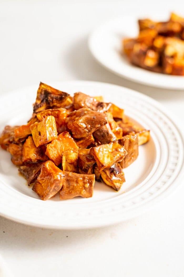 Miso glazed sweet potato on a small white plate.