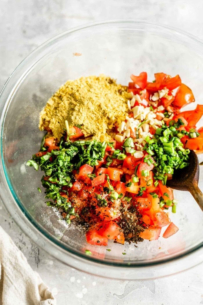 Vegan bruschetta ingredients in a mixing bowl.