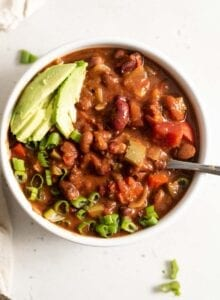 A bowl of vegan chili topped with avocado and green onion.