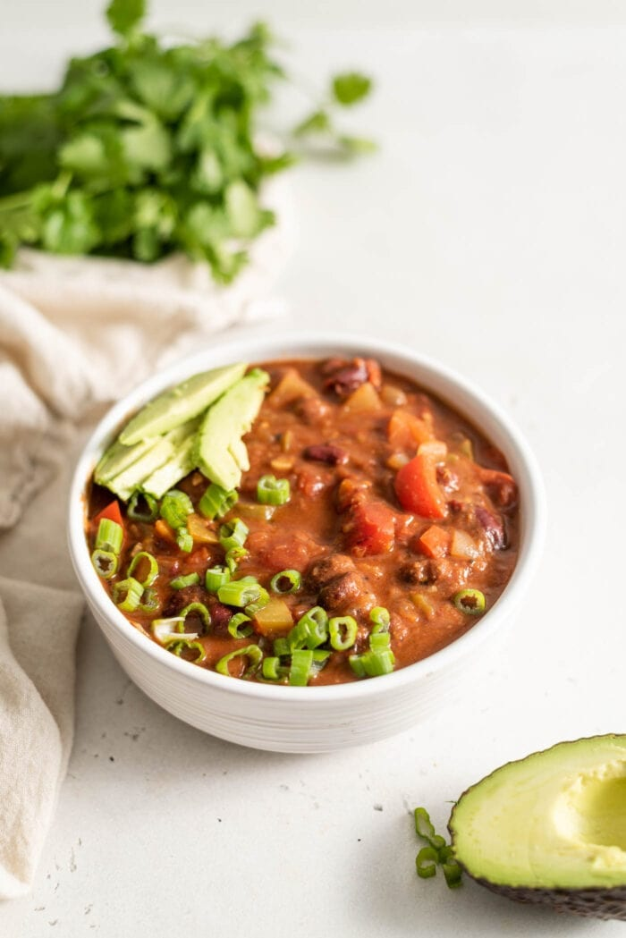 A bowl of vegan chili topped with avocado and green onion with half an avocado sitting beside it.