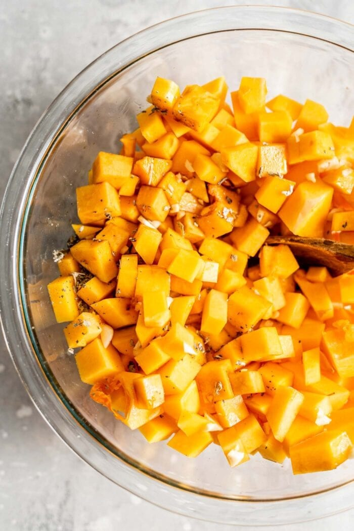 Cubed butternut squash in a mixing bowl with garlic, oil and vinegar.