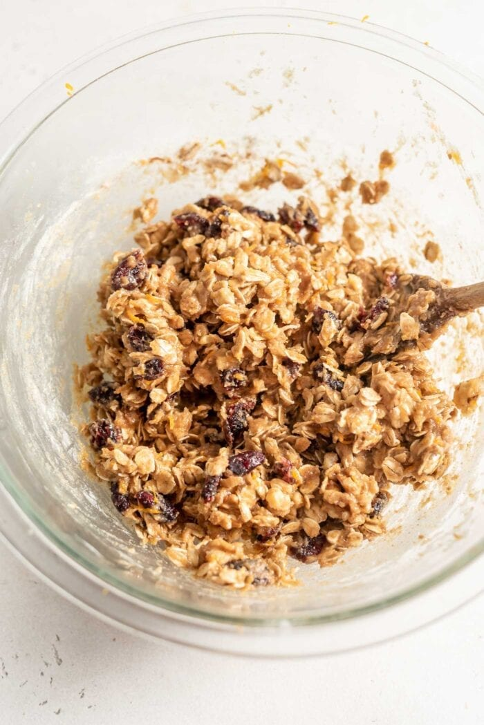 Raw cranberry orange oatmeal cookie dough in a glass mixing bowl.