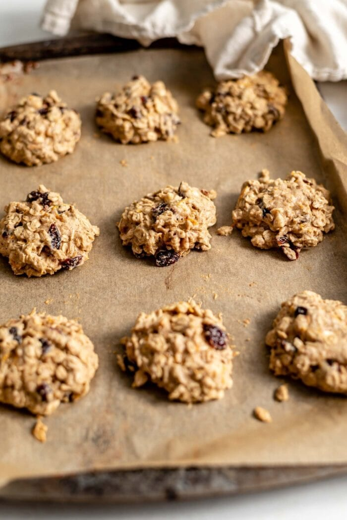 Baked cranberry orange oatmeal cookies on a parchment paper-lined baking tray.